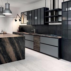 FACTORY to linia mebli kuchennych utrzymanych w industrialnym klimacie. Chromowane fronty zestawiono z eleganckim kamiennym blatem i akcentami z naturalnego drewna. Aster Cucine