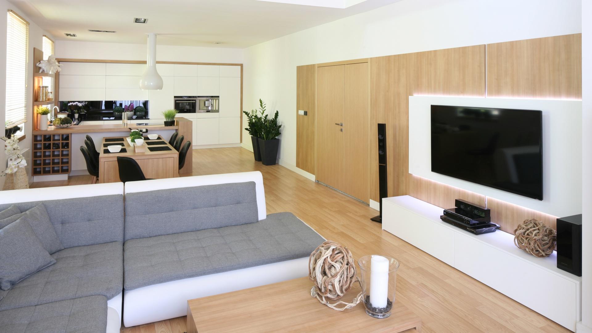 Cała ściana została wykończana płytą meblową z drewnopodobnym dekorem, dla kontrastu telewizor umieszczono na białym podświetlonym panelu. Projekt: Małgorzata Błaszczak. Fot. Bartosz Jarosz