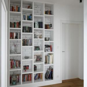 Biała ściana z cegły stanowi idealne tło dla regału z książkami i kolorowymi elementami dekoracyjnymi. Proj. wnętrza Monika i Adam Bronikowscy, Hola Design. Fot. Bartosz Jarosz.