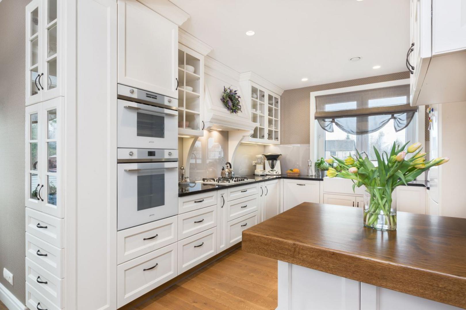 Klasyczny charakter aranżacji podkreślają stylizowane meble i frezowane fronty kuchenne.