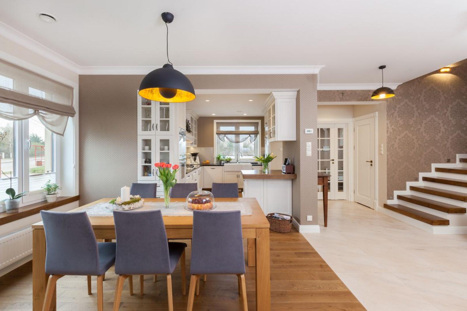 Koniakowy odcień podłogi efektownie kontrastuje z bielą ścian, drzwi i mebli kuchennych.