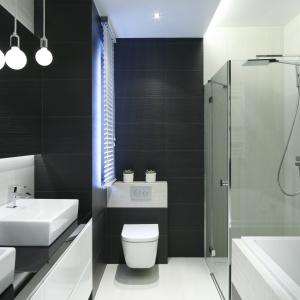W wąskiej łazience obszerna narożna kabina prysznicowa ustawiona została w jednej linii z wanną. Projekt: Karolina Stanek Szadujko, Łukasz Szadujko. Fot. Bartosz Jarosz