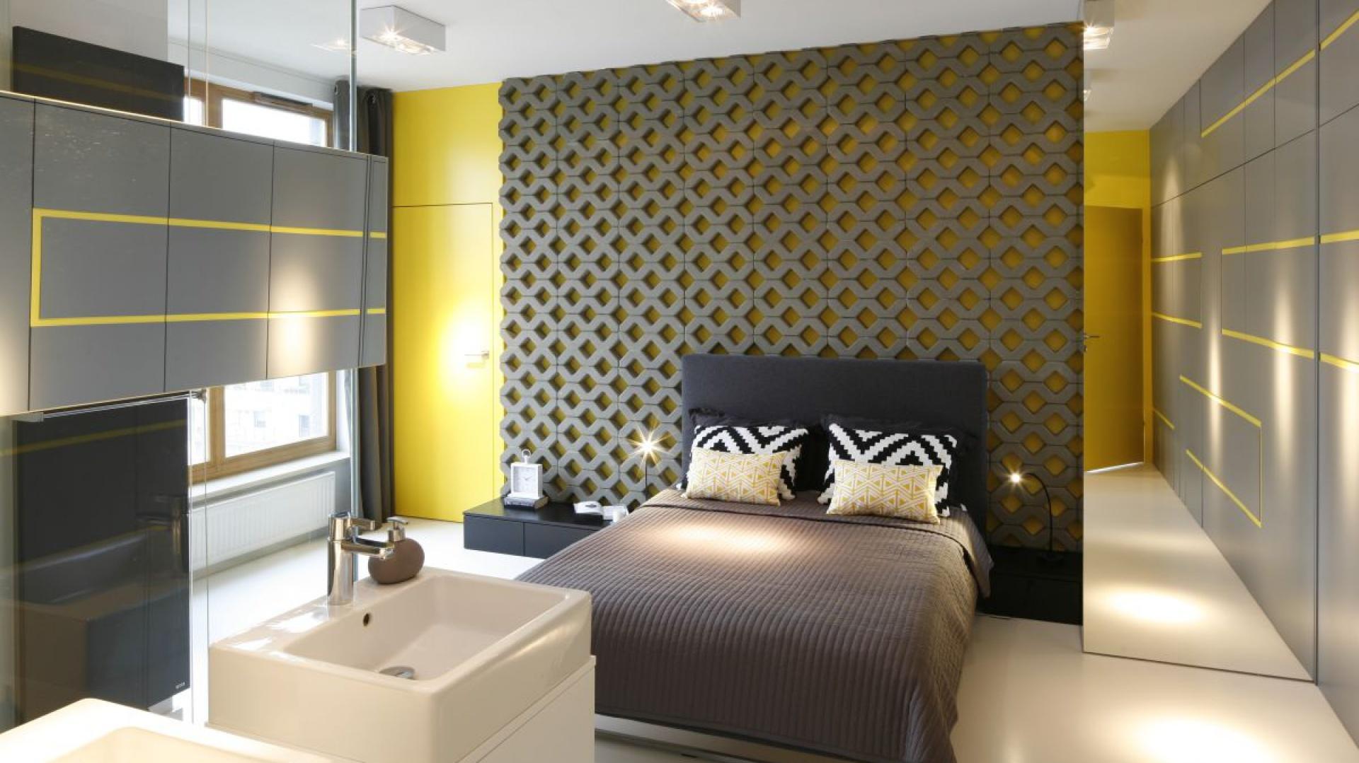 W centrum sypialni umieszczono duże, wygodne łóżko z nakryciem kolorystycznie łączącym się z kolorystyką ścian. Proj wnętrza Monika i Adam Bronikowscy, Hola Design. Fot. Bartosz Jarosz.