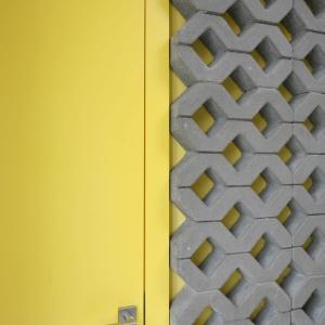 Kolor płyt kontrastuje z żółymi drzwiami wejściowymi do pomieszczenia. Proj. wnętrza Monika i Adam Bronikowscy, Hola Design. Fot. Bartosz Jarosz.