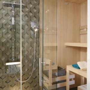 W sypialni wyodrębniono strefę wypoczynkową, w której zamontowano kabinę prysznicową  i saunę. Proj. wnętrza Monika i Adam Bronikowscy, Hola Design. Fot. Bartosz Jarosz.