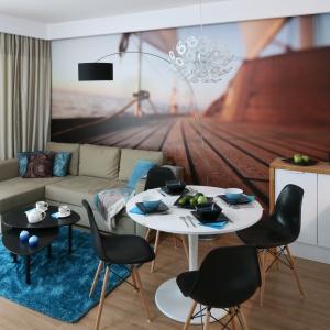 W małym salonie przestrzeń organizuje niewielki narożnik, a optycznie powiększa wnętrze fototapeta na ścianie. Projekt Anna Maria Sokołowska. Fot. Bartosz Jarosz