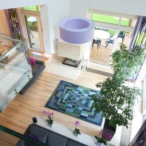 Kolorowy dywan w przestronnym salonie nawiązuje do barwy dodatków. Projekt: Monika i Adam Bronikowscy. Fot. Bartosz Jarosz