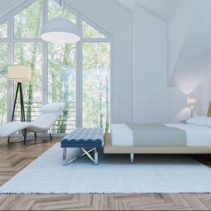 W minimalistycznie urządzonej sypialni z dużymi przeszkalaniami parkiet ociepla całe wnętrze. Fot. Z500