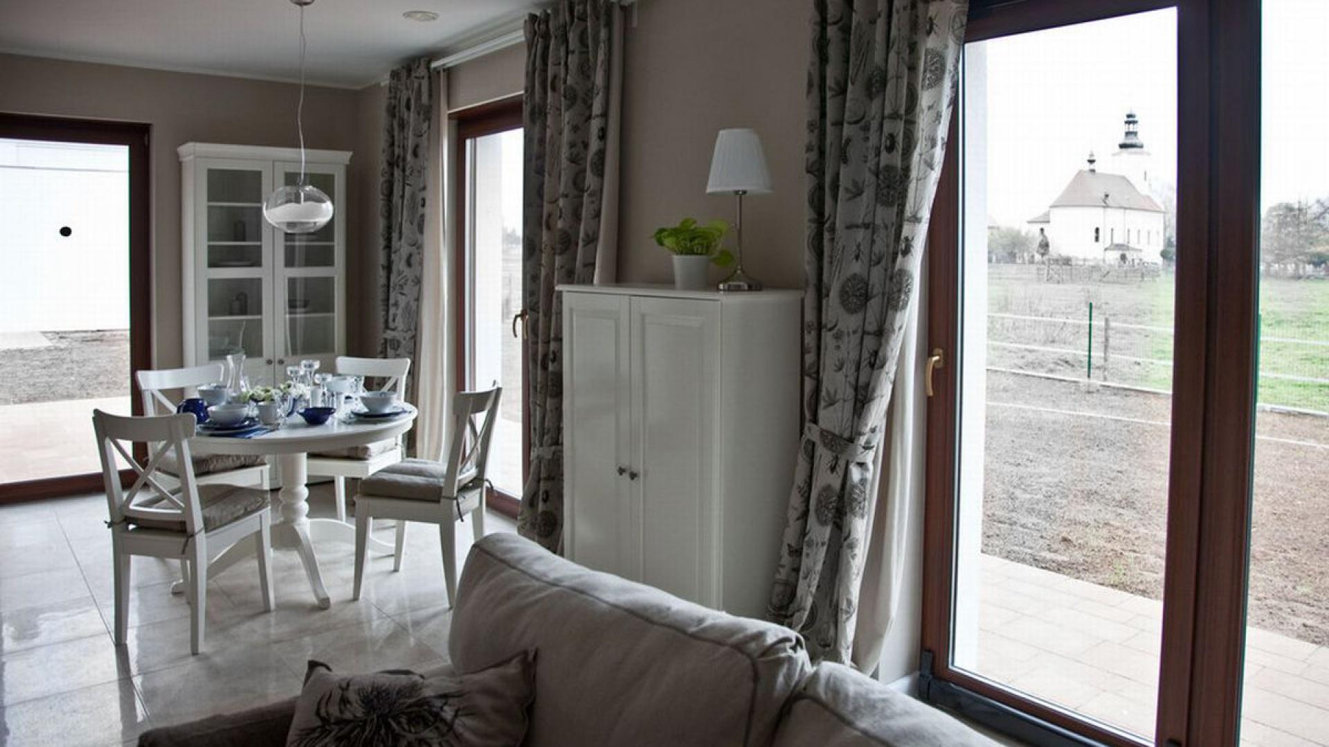 Szara kanapa i zasłony w podobnych odcieniach oraz naturalnie drewniana stolarka okienna są niezwykłą ozdobą wnętrza. Fot. Spółka Śląski Dom