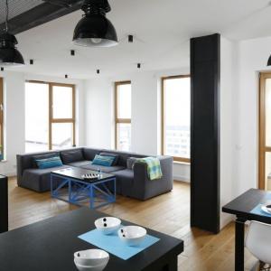 W salonie o charakterze loftu drewniane okna nie tylko zapewniają dużą dawkę słońca, ale też ocieplają to minimalistyczne wnętrze. Proj. Monika i Adam Bronikowscy, Fot. Bartosz Jarosz