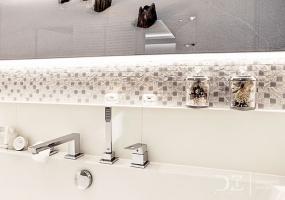 Nadruk w białej łazience oraz lustro na całej długości ściany pozwoliły optycznie powiększyć małe pomieszczenie. / fot. doriz pragmatic design