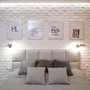 Sypialnia w nieco loftowym stylu z białą cegłą na ścinie za łóżkiem. Na jej tle dobrze wygląda szare łóżko. Proj. Marta Kramkowska, Fot. Bartosz Jarosz