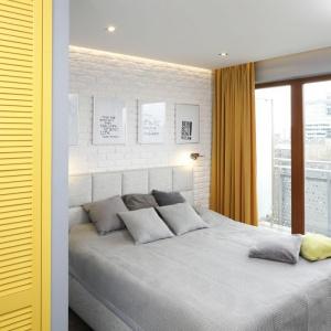 Do szarej sypialni warto wprowadzić akcent kolorystyczny. Tu zastosowano miodowe zasłony i żółte drzwi do garderoby. Proj. Marta Kramkowska, Fot. Bartosz Jarosz