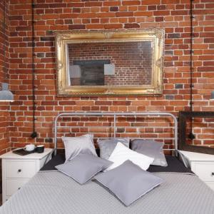 Czerwona cegła to dobre tło dla szarych dodatków w sypialni. Proj. Loft Nowa Papiernia, Fot. Bartosz Jarosz
