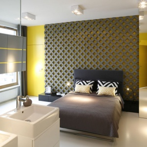 W tej sypialni na uwagę zasługuje ażurowa ściana za łóżkiem. Szarość połączono tu z żółtym, który nadaje wnętrzu niesamowitej energii. Proj. Monika i Adam Bronikowscy, Fot. Bartosz Jarosz