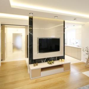 Naprzeciw szarego wypoczynku znajduje się ściana z telewizorem, która częściowo przysłania otwartą na salon kuchnię.