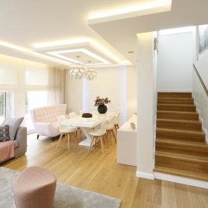 Równolegle do szarej sofy ustawiono elegancka sofkę w różowym kolorze, która z jednej strony stanowi przedłużenie części salonowej, z drugiej optycznie zamyka przestrzeń jadalni.