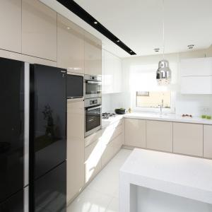 Kuchnia, choć otwarta, pozostaje nieco przysłonięta. Urządzona w bieli i kolorze kawy z mlekiem stanowi reprezentacyjne tło dla salonowej aranżacji.