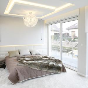 Główna sypialnia właścicieli to swoista oaza spokoju. Gwarantują go stonowane brązy, miękkie tkaniny oraz piękne widoki przez duże przeszklenia.