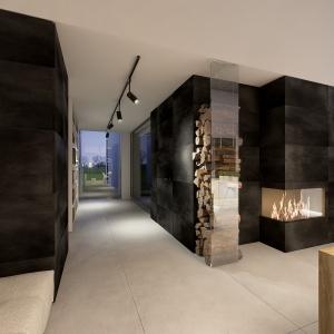 Czarna ściana kominkowa wykończona wielkoformatowymi płytkami stanowi idealne tło dla płonących szczap.