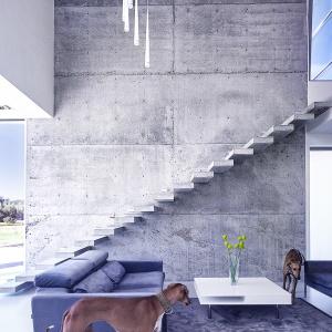 Dom posiada przestronną - 5 m wys. strefę dzienną, którego główną ozdobą jest ściana i schody wspornikowe wykonane z betonu architektonicznego. Fot. BXBstudio Bogusław Barnaś