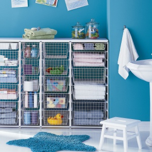 Zestaw koszy kolorze białym Elfa; na prowadnicach, wysuwane jak szuflady; wolno stojący zestaw można umieścić w dowolnym miejscu łazienki lub pralni; praktyczny sposób na organizację i przechowywanie w łazience. Fot. Elfa
