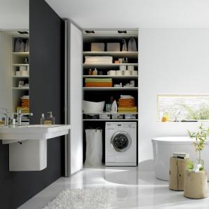 Łazienka z kącikiem na pranie ukrytym za skałdanymi drzwiami. Fot. Raumplus
