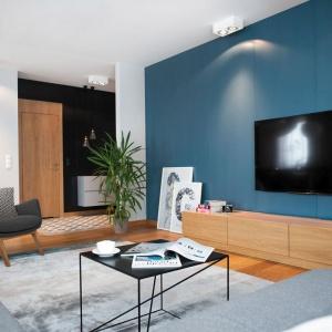 Podstawowym elementem wystroju apartamentu stało się naturalne, dębowe drewno. Tworzy ono fenomenalną oprawę całego wnętrza i doskonale równoważy wszystkie chłodne akcenty. Fot. Adam Ościłowski