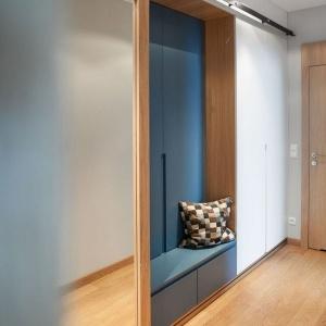 """W długiej szafie z przesuwnym lustrem zastosowano nietypowy system drzwi """"Barn Door"""", za którymi znalazło się miejsce na siedzisko umieszczone w niewielkiej niszy, ułatwiające zakładanie butów lub odpoczynek. Fot. Adam Ościłowski"""