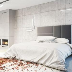 Sypialnia to praktycznie jedna, otwarta przestrzeń z możliwością wydzielenia pomieszczeń przesuwnymi drzwiami. Dominuje tu stonowana kolorystyka, podkreślona betonową ścianę z kominkiem, który został obłożony płytami gresowymi. Fot. 81.WAW.PL
