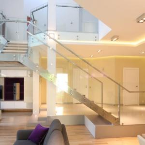 Schody, w zależności od koncepcji na urządzenie wnętrza naszego domu, możemy pięknie wyeksponować lub ukryć. Tu dzięki szklanym balustradom i modnym stalowym wykończeniom schody prezentują się niezwykle pięknie. Projekt: Monika i Adam Bronikowscy, Fot. Bartosz Jarosz