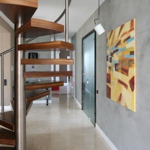 Schody spiralne są mniej wygodne niż dwubiegowe, jednak za ich wyborem przemawia wspomniany niewielki rozmiar, łatwość montażu, możliwość lokalizacji zarówno przy ścianie, jak i w centrum salonu oraz atrakcyjny wygląd. Projekt: Katarzyna Koszałka, Fot. Bartosz Jarosz