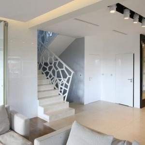 Tu schody ukryto w klatce schodowej. Jednak ozdobiono je efektowną ażurową balustradą. Projekt: Agnieszka Hajdas-Obajtek, Fot. Bartosz Jarosz