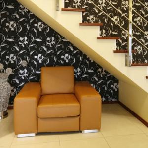 Jednobiegowe schody o jasnej barwie ciekawie prezentują się na tle ciemnej ściany. Pod nimi znalazła się przestrzeń na kącik wypoczynkowy. Projekt: Piotr Stanisz, Fot. Bartosz Jarosz