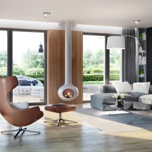 Ważna miejsce w salonie zajmuje designerski podwieszany kominek w białym kolorze. Z kolei duże przeszklenia naturalnie łączą dom z ogrodem. Fot. Pracownia Projektowa Archipelag