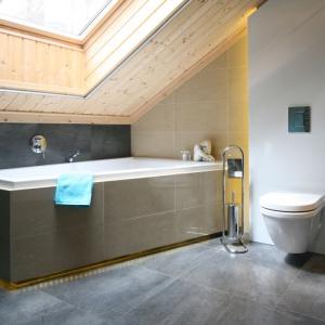 Małe łazienki przeważnie umiejscowione są na poddaszu, gdzie ograniczeniem są również skosy. Tu ścianę dachową wykończono drewnem i podświetlono wannę, co nadało łazience niepowtarzalnego uroku. Projekt: Tomasz Motylewski, Marek Bernatowicz, Fot. Bartosz Jarosz