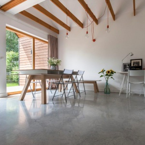 Po prawej stronie naprzeciwko drzwi balkonowych mamy duży jadalniany stół z ławą i lekkimi krzesłami. Fot. Bautech Futura