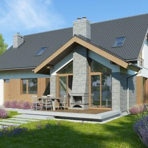 Za pomocą kamienia pięknie wyeksponowano detale architektoniczne: komin i duże przeszklenia fasady ogrodowej. Proj. Telimena II, Fot. Dobre Domy