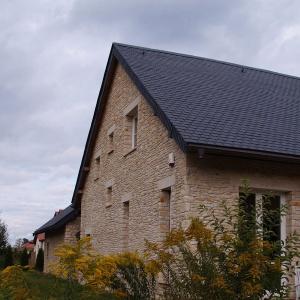 Łupek kamienny na dachu i dolomit na elewacji zastosowano w domu w Strzeniówce. Przepięknie prezentuje się w sielskim otoczeniu. Fot. S&O Projekty Sylwii Strzeleckiej