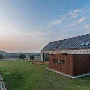 """Gabionowy """"dom w krajobrazie"""" stworzony przez Kropka Studio został wykończony w tej technice niemal w całości. Wyjątkiem jest wyraźnie oddzielona od głównej bryły budynku sypialnia wykończona deskami, a także trójkątny wykusz z boku domu. Fot. Kropka Studio"""