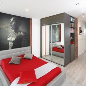 Szarość będącą kolorem przewodnim w sypialni doskonale ożywia czerwień w dodatkach. Projekt: Monika Olejnik. Fot. Bartosz Jarosz