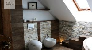 Utrzymana w kolonialnym stylu łazienka autorstwa pracowni Arte-Interni to realizacja umiejętnie łącząca naturalne drewno, płytki drewnopodobne oraz kamień z elegancką ceramiką oraz armaturą łazienkową.