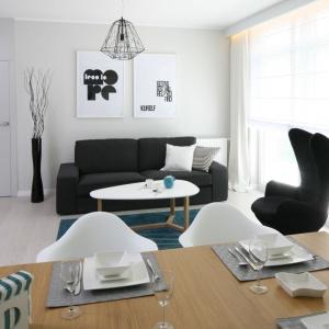 Salon również utrzymany jest w jasnej kolorystyce. Czerń i biel oraz turkusowe dodatki zostały tu bardzo estetycznie skomponowane. Projekt: Anna Maria Sokołowska, Fot. Bartosz Jarosz