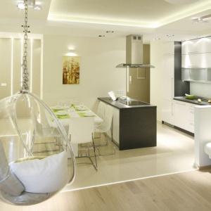 Biele i beże to naturalne kolory w niewielkich wnętrzach. Funkcjonalną granicę pomiędzy salonem i kuchnią wyznacza linia płytek ceramicznych stykających się z parkietem. Projekt: Marta Kilan, Fot. Bartosz Jarosz