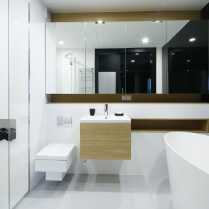 Salonik kąpielowy z prysznicem i wolno stojącą wanną oddzielają od sypialni przesuwne drzwi z grafitowego szkła. Fot. Bartosz Jarosz