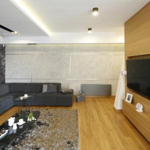 Aranżacja salonu jest na wskroś nowoczesna. Przestrzeń wypełniają odcienie szarości, dla których efektowny kontrast stanowi biel, a całość ociepla dodatek drewna w postaci forniru dębowego. Fot. Bartosz Jarosz