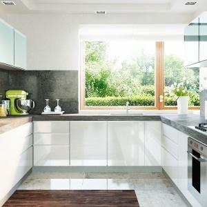 W kuchni rządzi porządek i codzienna wygoda. Szeroki blat roboczy, praktyczny zestaw szaf oraz duże okno doświetlające strefę gotowania. Fot. Pracownia Projektowa Archipelag
