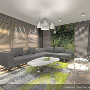 W salonie jasna tonacja kolorystyczna drewnianej podłogi doskonale komponuje się z białymi ścianami. Tylko na jednej płaszczyźnie zaproponowano przełamanie szarości soczystą zieloną fototapetą. Projekt: Aksamit 2, arch. Tomasz Sobieszuk, Biuro Projektów MTM Styl