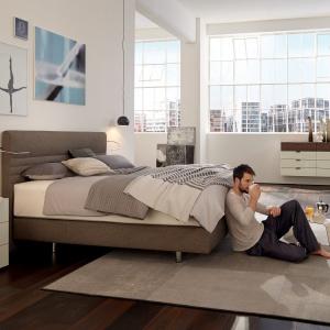 Wygodne i efektowne łóżko kontynentalne SUITE HOME o nowoczesnym designie. Tapicerowane tkaniną w modnym odcieniu szarości. Na zamówienie. Fot. Hülsta