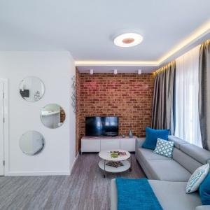 """Salon został zaprojektowany jako przestrzeń do relaksu. Centralnym miejscem jest """"ceglana"""" ściana. Zdjęcia: Nowa Papiernia, Fot. Maciej Lulko"""